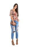 Young casual shy beauty posing while holding handbag smiling at camera Stock Photo