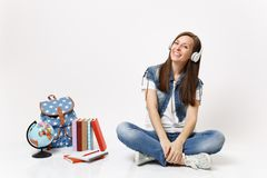Young casual smiling happy woman student with headphones listening music sitting near globe, backpack, school books royalty free stock image