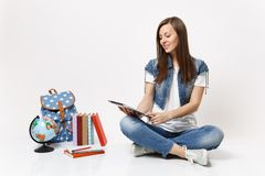 Young casual smiling woman student in denim clothes holding using tablet pc computer sitting near globe backpack school. Books isolated on white background royalty free stock images