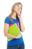 Young casual student holding workbook and thinking. Royalty Free Stock Photography