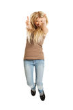 Young casual student jumping showing thumbs up Stock Image