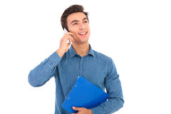 Young casual student talking on the phone and holds clipboard. On white background Royalty Free Stock Image