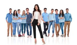 Young casual team with businesswoman leader standing in front. Young casual team wearing blue shirts with businesswoman leader standing in front of them on white stock image