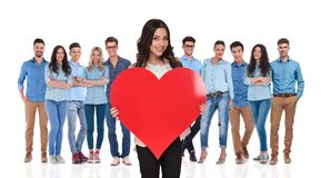 Young casual team celebrating valentine`s day with businesswoman. Young casual team celebrating valentine`s day with their businesswoman leader holding a red royalty free stock image