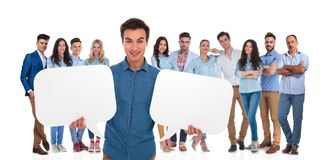 Young casual team leader holding two empty speech bubbles stock photos
