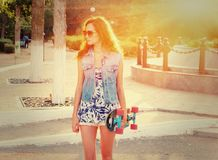 Young casual weared woman standing with skateboard in her hands Royalty Free Stock Image