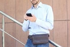 Young casual wearing man with modern leather waist bag standing royalty free stock images