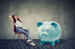 Woman with big piggy bank relaxing sitting on chair Royalty Free Stock Image