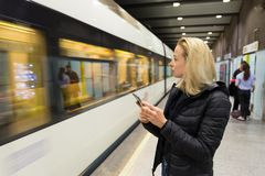 Woman with a cell phone waiting for metro. Young casual woman with a cell phone in her hand waiting on the platform of a metro station for metro to arrive Stock Photography