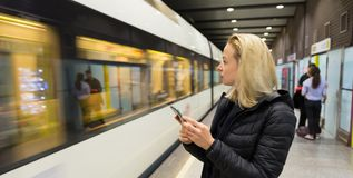 Woman with a cell phone waiting for metro. Young casual woman with a cell phone in her hand waiting on the platform of a metro station for metro to arrive Stock Image