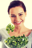 Young casual woman eating lamb's lettuce. Stock Images