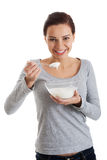 Young casual woman eating a yoghurt. Stock Image