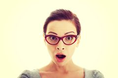 Young casual woman in eyeglasses expresses shock. Royalty Free Stock Images