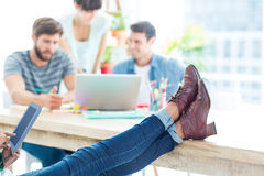Young casual woman with feet on the table Stock Photography