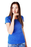 Young casual woman with finger on lips. Stock Images