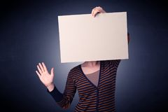 Woman holding blank paper. Young casual woman hiding behind a blank piece of paper Stock Image