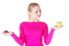 Young casual woman holding an apple and cookie. Stock Image