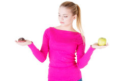 Young casual woman holding an apple and cookie. Royalty Free Stock Image