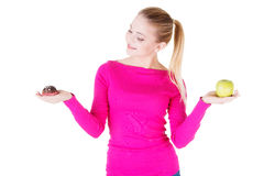 Young casual woman holding an apple and cookie. Stock Photography