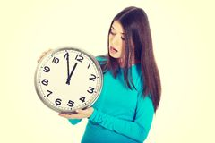 Young casual woman is holding a clock. Royalty Free Stock Images