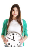 Young casual woman holding clock. Royalty Free Stock Photo