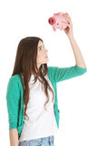 Young casual woman holding piggy-bank. Stock Photography