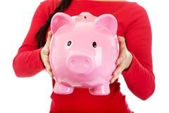 Young casual woman holding a piggybank Stock Photos