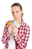 Young casual woman holding pills. Royalty Free Stock Images