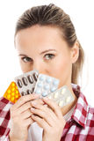 Young casual woman holding pills. Royalty Free Stock Photos