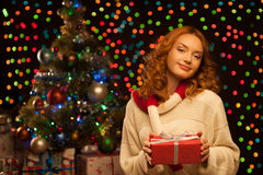 Young casual woman holding red christmas gift. Young casual woman holding red gift over christmas tree and lights on background. shallow depth of field. soft Stock Images