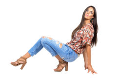 Young casual woman in jeans and high heels posing on the floor. Royalty Free Stock Photos