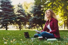Young casual woman with laptop and notebook outdoors. Young casual woman with laptop and tablet outdoors. Female student preparing for exams with computer, books Stock Photo
