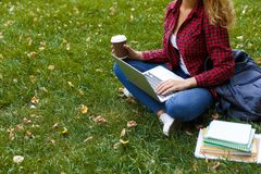 Young casual woman with laptop outdoors. Female student preparing for exams with computer, books and coffee in the park. Education and entering the university Stock Photography