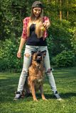 Young casual woman play with dog in garden Royalty Free Stock Images