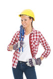 Young casual woman with plubmer wrench and safety helmet. Royalty Free Stock Photography