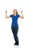 Young casual woman pointing up. Royalty Free Stock Photo
