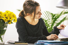 Young casual woman reviewing some documents in office. stock photography