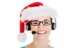Young casual woman in santa hat and,microphone and headphones. Isolated on white Stock Image