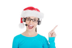 Young casual woman in santa hat and,microphone and headphones. Isolated on white Royalty Free Stock Photo