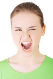 Young casual woman screaming with anger. Isolated on white Stock Photo