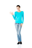 Young casual woman showing welcome gesture. Royalty Free Stock Photo