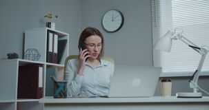 Young casual woman sitting at desk using laptop, answering call, talking on the phone, smiling teen speaking on mobile stock video footage