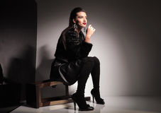 Young casual woman sitting on a stool Royalty Free Stock Image