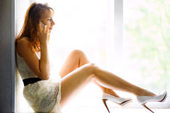 Young casual woman sitting on window and smiling Royalty Free Stock Photos