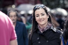 Young casual woman smiling at camera in a busy street Royalty Free Stock Photography