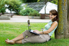 Young casual woman student in the park working on laptop Royalty Free Stock Photography