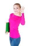 Young casual woman student showin OK gesture. Royalty Free Stock Images