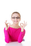 Young casual woman student showin OK gesture. Royalty Free Stock Photography
