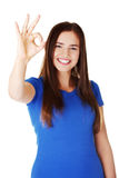 Young casual woman student showin OK gesture. Royalty Free Stock Photos
