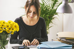 Young casual woman using digital tablet in office. Stock Photo